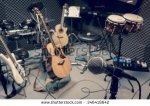 stock-photo-selective-focus-microphone-and-blur-musical-equipment-guitar-bass-drum-piano-background-346418642
